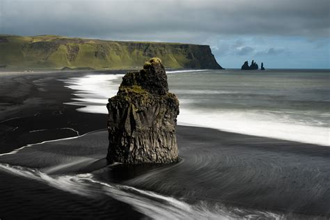 black sand game a basalt sea stack on a black sand beach in iceland 1600