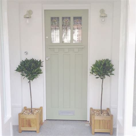 front door painted in a dulux colour match to farrow and lichen bay trees either side