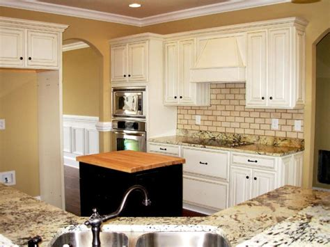 How To Distress White Kitchen Cabinets White Glazed Cabinets Distressed Hardwood Floors And Black Kitchen Island On