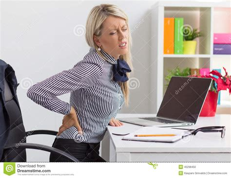 back pain from sitting at desk woman having back pain while sitting at desk in office
