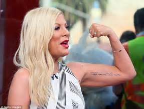 tori spelling tattoo spelling flexes biceps during tv appearance to