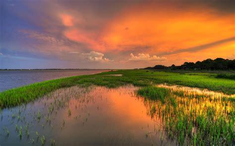 sunset red sky river field  green grass hd wallpaper