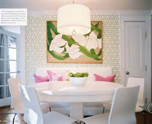 The wallpapered wall round white table and a few chairs damn