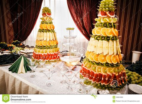 Dinner Party Table Setting by Champagne Fountain And Decorations From Fruit On Table