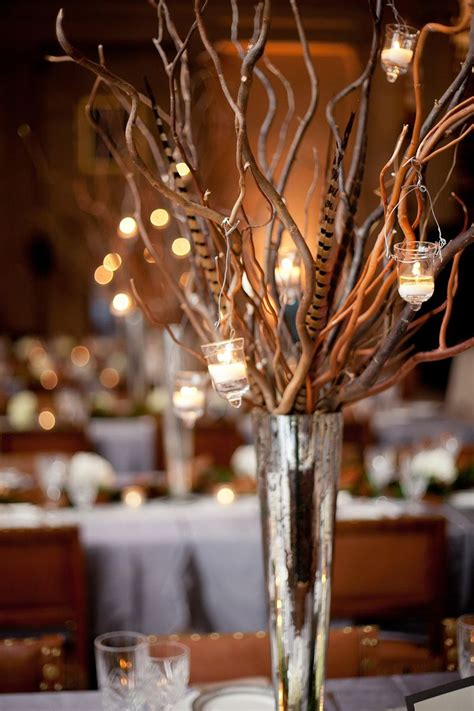 fall centerpieces with feathers twig and feather arrangement in mercury glass vase with