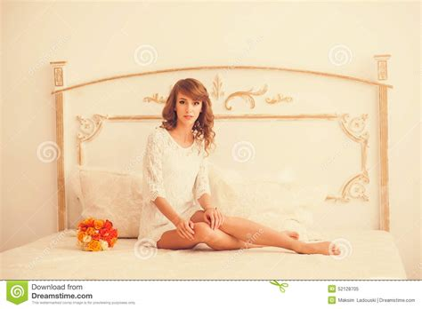 girl sitting on bed cute girl sitting on a bed in a dress stock photo image