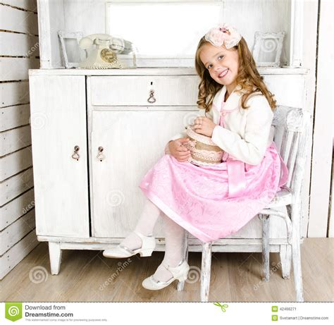 little girl on chair adorable little girl sitting on chair with gift box stock