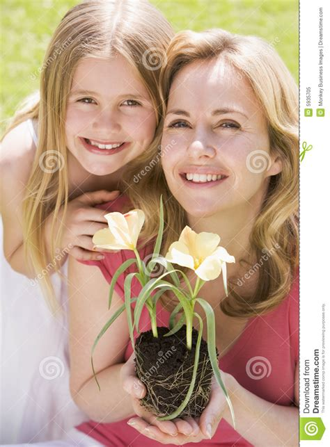 mamas comparten novio con hija madre e hija al aire libre que sostienen la flor imagen de