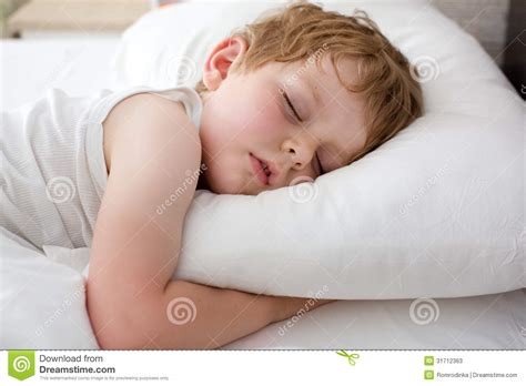 sleeping in bed little sweet toddler boy sleeping in his bed stock photos