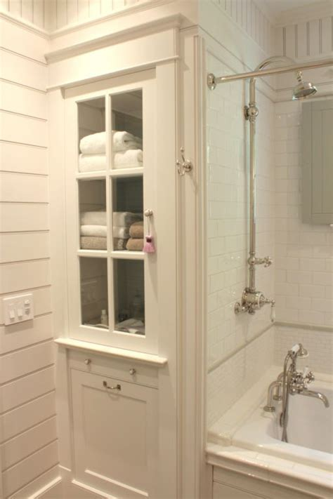 bathroom linen cabinet and tub surround with white subway