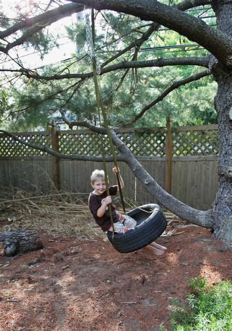 a tire swing hanging from a branch kids outdoor play spaces stately kitsch