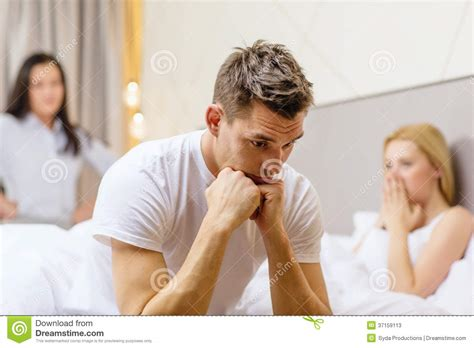 men in bed with other men man sitting on the bed with two women on the back stock photos image 37159113