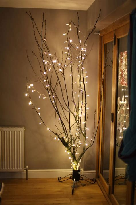 decorative tree branches with lights keep the glow alive with these winter decor ideas