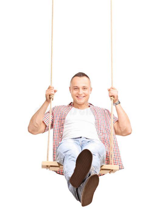 swinging man carefree young man swinging on a swing stock photo image