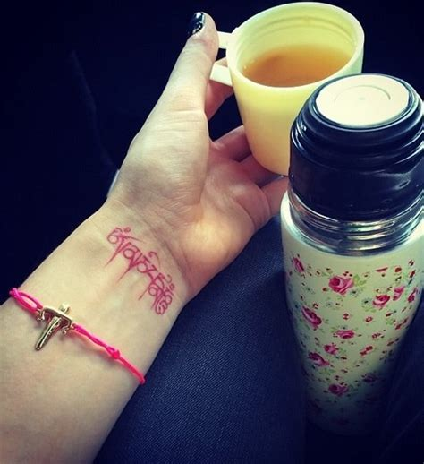 ellie goulding s red wrist tattoo of a tibetan mantra