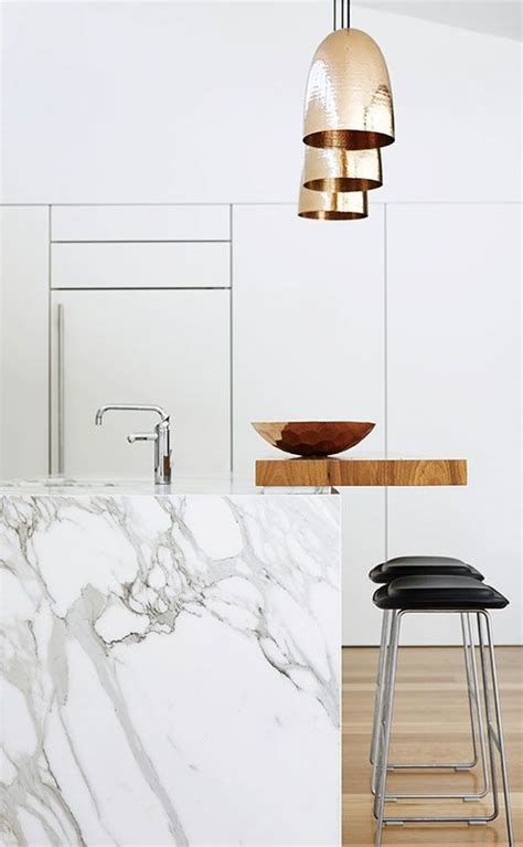 white marble kitchen island with black bar stools and gold