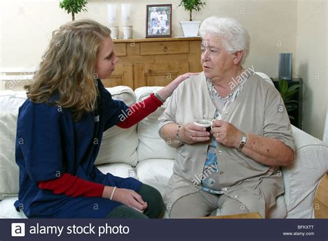 buying a house with another person young district nurse talking with old lady helping older person at stock photo