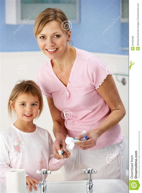 mom in bathroom mother and daughter cleaning teeth in bathroom royalty