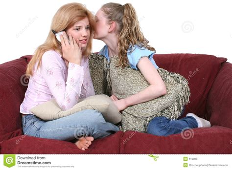 two girls having on the couch best friends gossiping on the phone sitting on couch stock