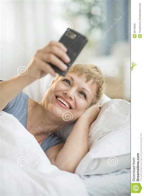 phone in bed cheerful woman using smart phone in bed stock photography