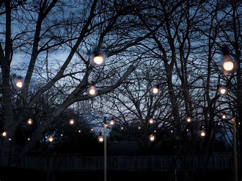 hanging lights in backyard how to hang outdoor string lights from diy posts hgtv