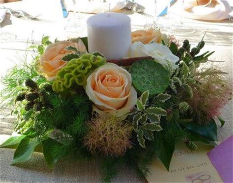 composizione di candele centrotavola tondo con fiori freschi di stagione e candele