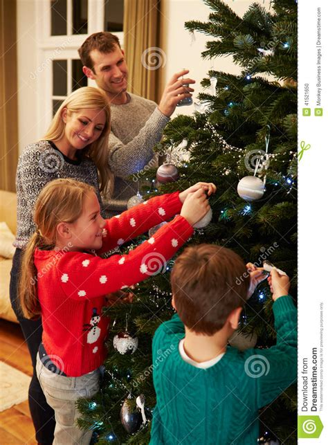 decorating with family photos family decorating christmas tree at home together stock