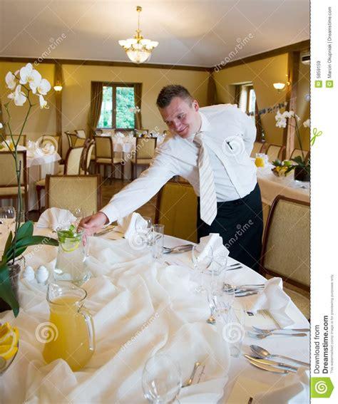 waiter setting table stock image image  furnished dinnerware