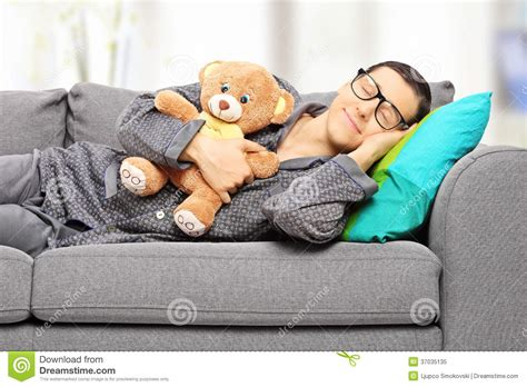 napping couch young man holding teddy bear and taking a nap on couch
