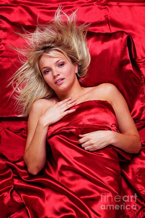 women in bed beautiful blonde woman in a bed of red silk sheets photograph by richard thomas