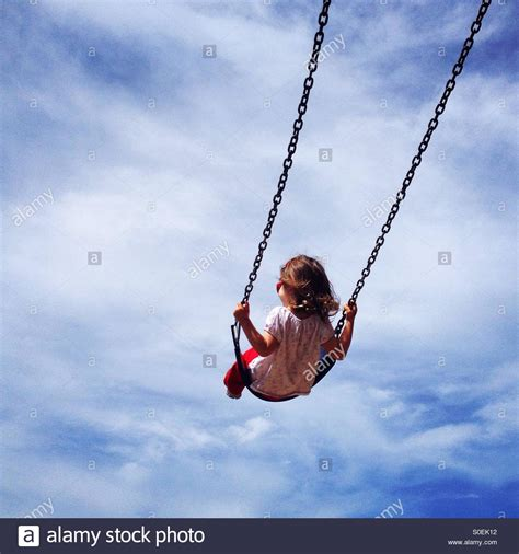 children swinging child swinging into a blue sky stock photo royalty free