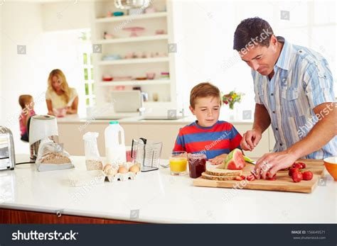 family in kitchen son helping father prepare family breakfast stock photo