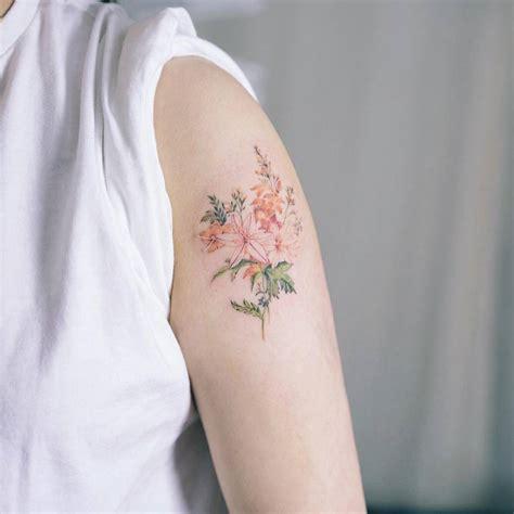 flower tattoo on upper arm illustrative style flower tattoo on the left upper arm