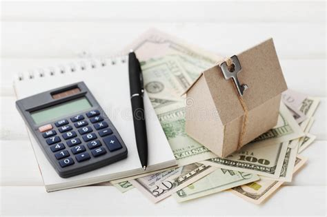 house buying cost calculator model of cardboard house with key calculator notebook pen and cash dollars house building