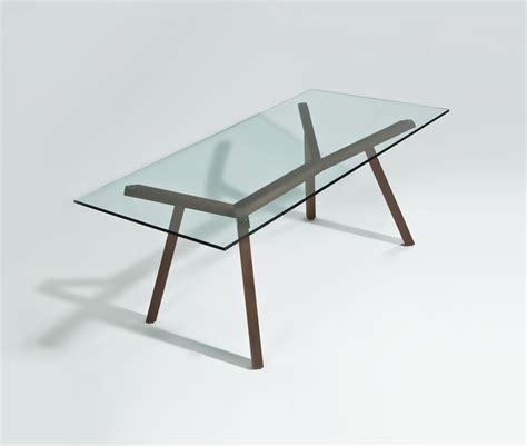 a modern dining table with glass top made to impress
