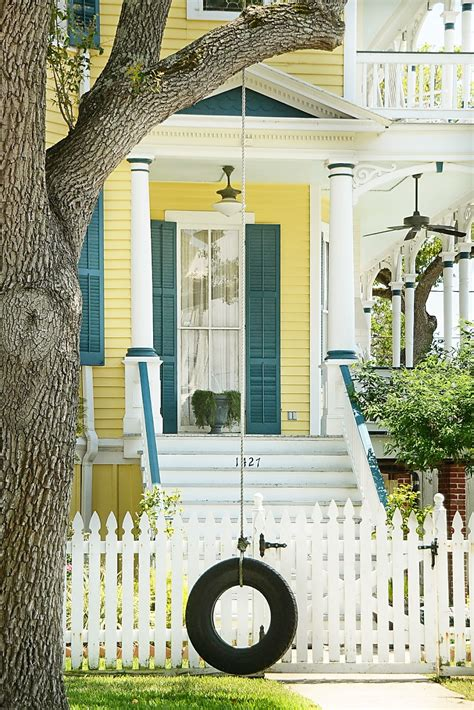 yellow house with blue door white picket fences country houses blue shutters blue