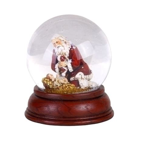 kneeling santa snowglobe with cherry base the catholic