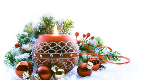 Christmas Floral Centerpiece Ideas - white candles in the glass with green leaves and red fruits f ornament placed on middle of brown