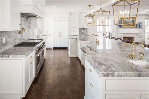 white and gold kitchen features white cabinets adorned white and gray kitchen features white shaker cabinets adorned with brass hardware paired with