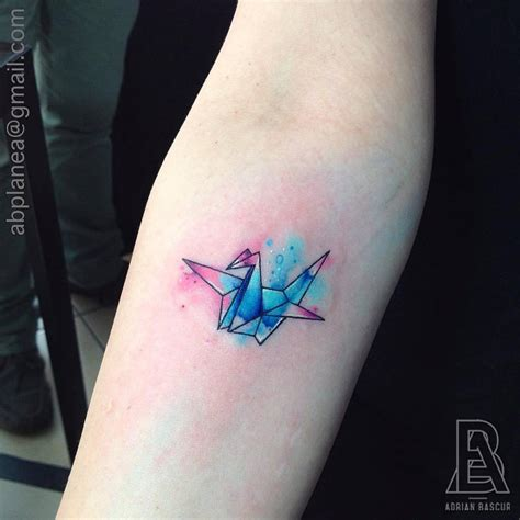 minimalist watercolour tattoo forearm tattoo of an origami crane with a watercolor