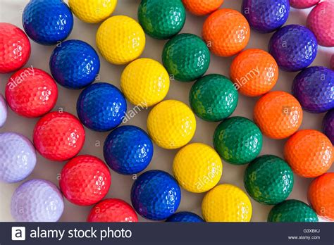 rows of colorful mini golf balls on white background stock