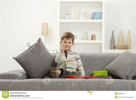 sitting sofa happy little kid with toys sitting on sofa stock photo
