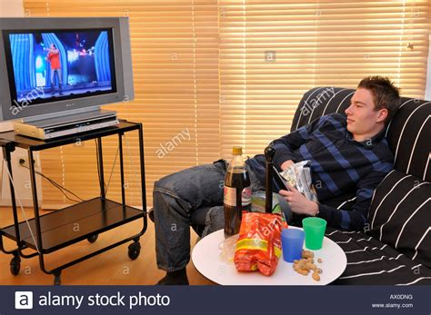 couch online tv teenager sitting on couch watching tv stock photo royalty