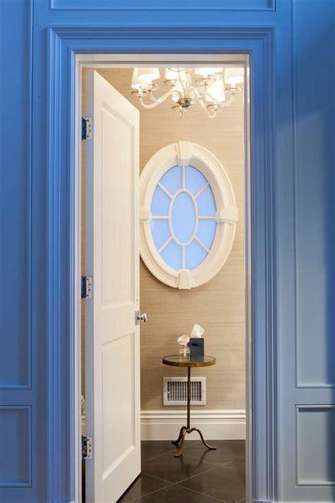 good Powder Room Decor Ideas #4: powder-room-oval-window-brass-accent-table-black-marble-floor.jpg