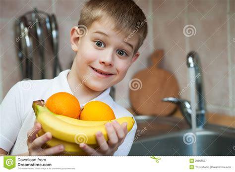les gar輟ns dans la cuisine le petit gar 231 on lave le fruit dans la cuisine photographie