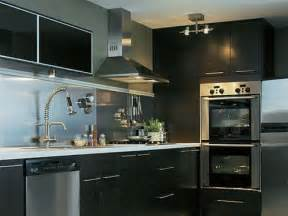 kitchen with black cabinets and stainless steel backsplash