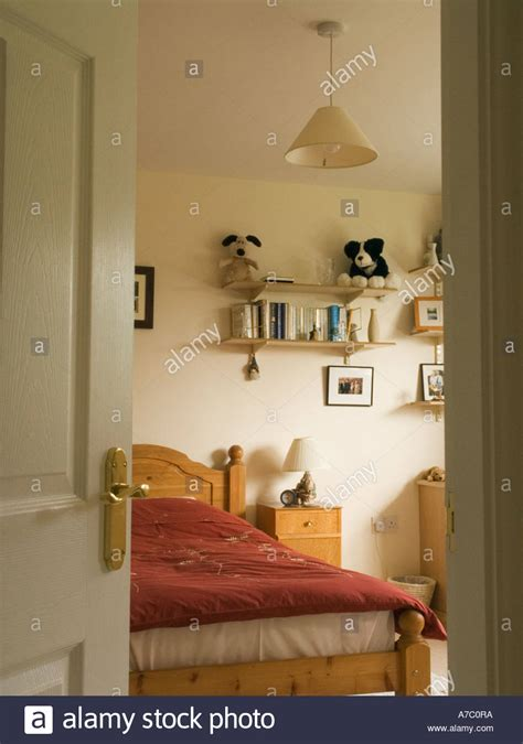 buy a bedroom door view through a bedroom door with bed and furniture inside a house stock photo royalty