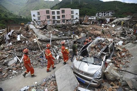 earthquake in china rescue workers walk past debris of houses at an earthquake