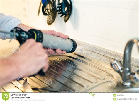 the kitc of worker using a silicone for repairing in the kitc stock photo image of house