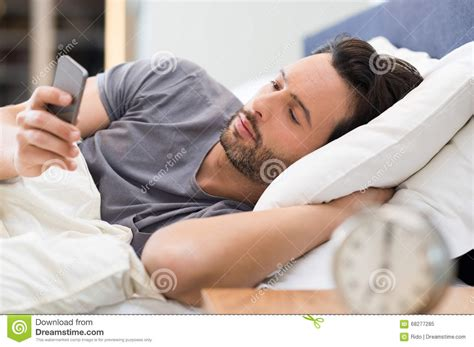 phone in bed man checking phone in bed stock photo image 68277285